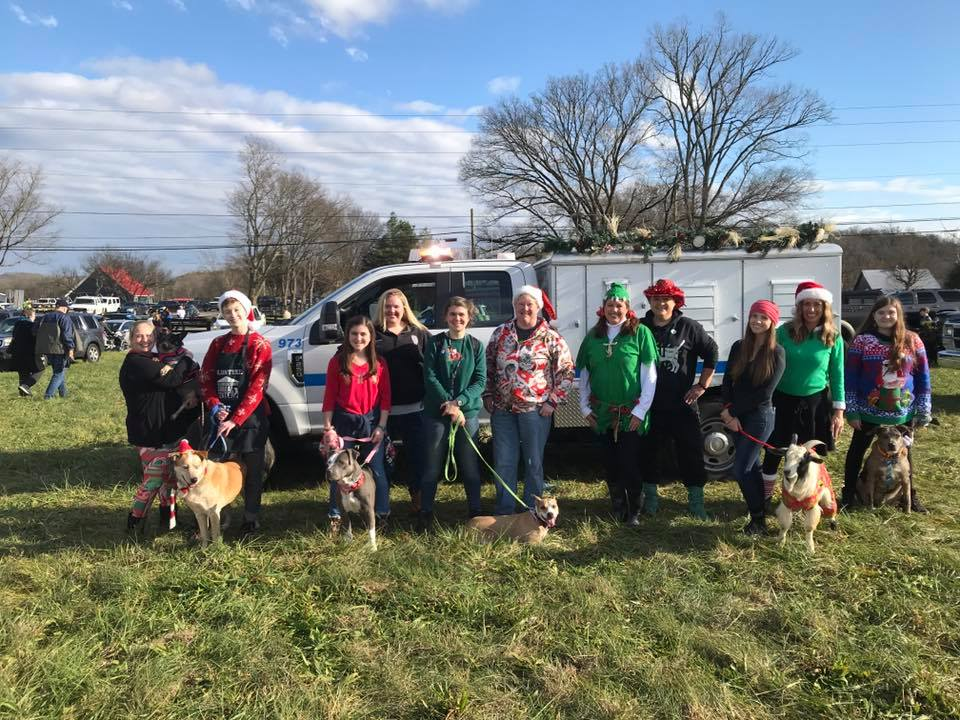 WCAC staff and volunteers with dogs and a holiday themed animal control truck
