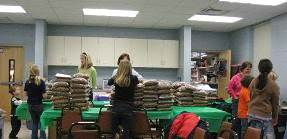 Girl Scouts volunteers package food for the paws on wheels program.